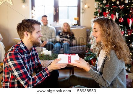 Young friends at decorated Christmas tree celebrating Christmas together exchanging gifts. Hipster man giving gift to beautiful young woman.