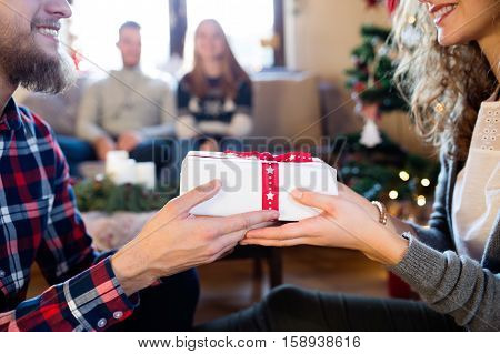 Young friends at decorated Christmas tree celebrating Christmas together exchanging gifts. Unrecognizable hipster man giving gift to beautiful young woman.