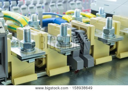 beige bolt bushing terminals on the DIN rail located on the mounting panel is connected to them wires fixed retainers