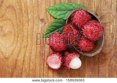 Natural organic lychee fruit (rambutan) on a wooden table