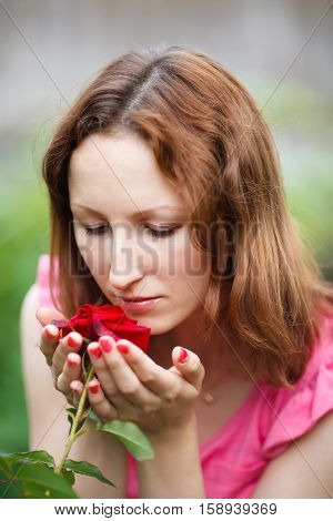 Portrait of young woman smelling red rose in garden