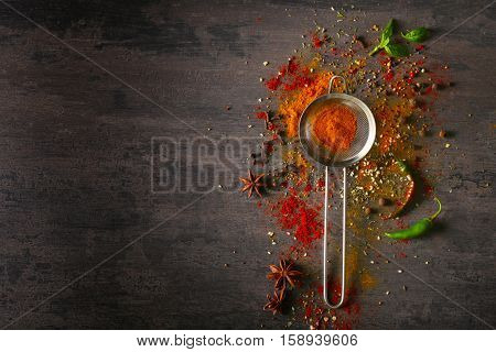 Assortment of spices and sieve on grey background