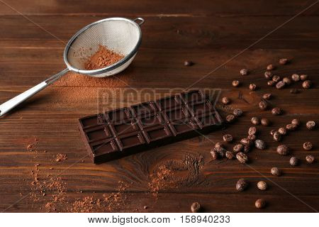 Chocolate with sieve and beans on wooden table