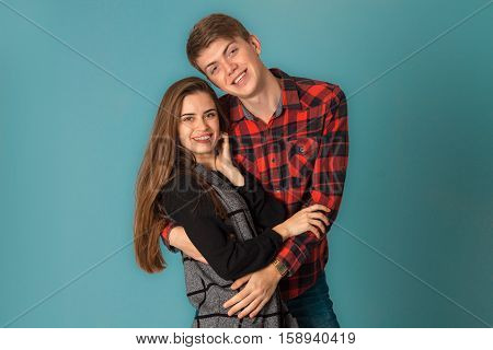 close up of attractive stylish couple in love having fun in studio on blue background