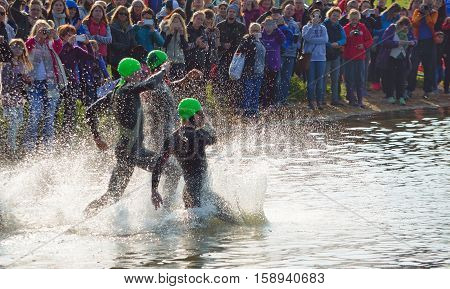 GRAFHAM, CAMBRIDGESHIRE, ENGLAND - MAY 22, 2016:  Triathlon swimmers entering open water swim stage.