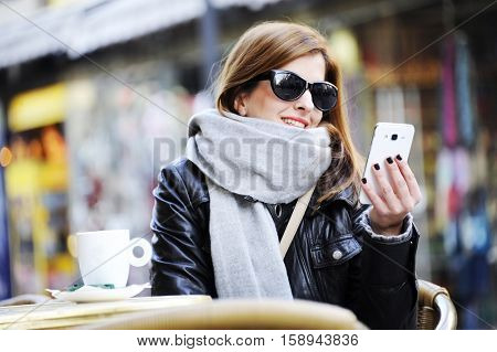 Young woman sitting at the street cafe , drinking coffee and using mobile phone with street life in winter time. Lifestyle concept
