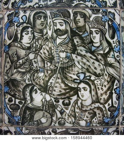 ISFAHAN, IRAN - OCT 15, 2014: Women with Persian king have fun on 19th century ceramic tile on October 15, 2014 in Middle East. Third largest city in Iran Isfahan is outstanding example of Islamic culture