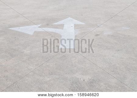 Closeup surface old and pale white painted arrow sign on cement street floor textured background with copy space