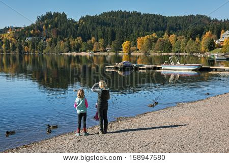 Woman with a child on the shore of Titisee  Lake  in  autumn, Germany