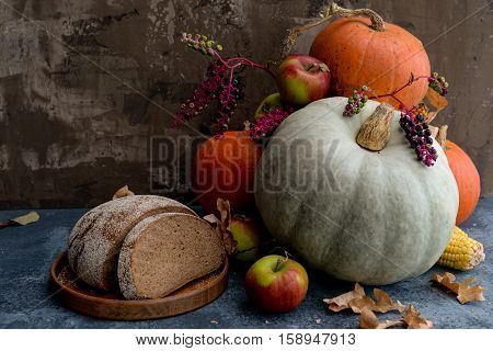 Autumn composition with autumn fruits, corn and pumpkins