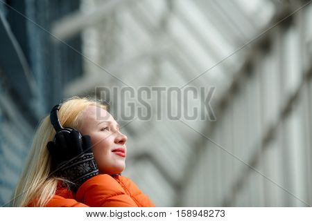 Girl in orange jacket enjoying music on headphones indoors