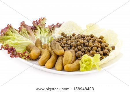 Marinated pickled cucumbers capers and lettuce on plate.