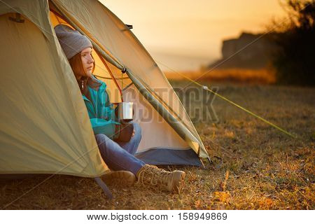 Young beautiful woman in colorful sports wear and trekking shoes sitting in light olive bivouac with metal mug in hands at autumnal landscape background with sunset sunlight and mountains at the horizon