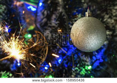 Cristmas toy and bengali fire on background of the festoon and fir trees