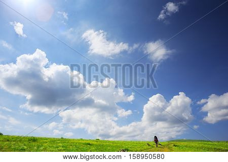 Tourist with a backpack walks on the trail through the field with green grass at scenic summer landscape with sunlight and hills at the horizon under blue cloudy sky