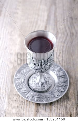 Silver kiddush cup with wine on the wooden table