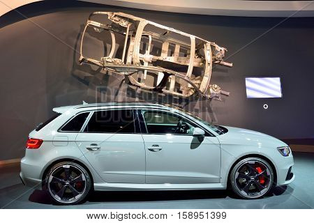 Wolfsburg, Germany - April 15, 2016. Audi RS3 car on display at Audi permanent showroom in Autostadt theme park in Wolfsburg. Side view of the car with body framework hanging above.