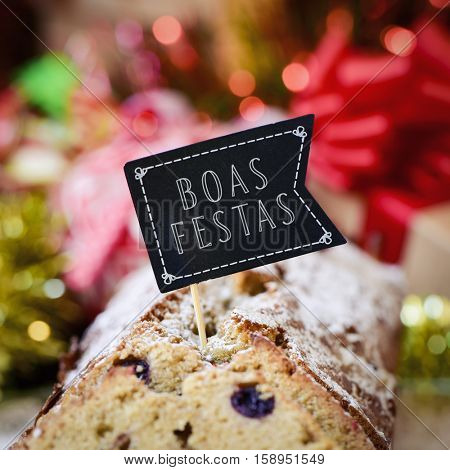 closeup of a fruitcake topped with a flag-shaped signboard with the text boas festas, happy holidays written in portuguese, on a table full of christmas gifts and ornaments
