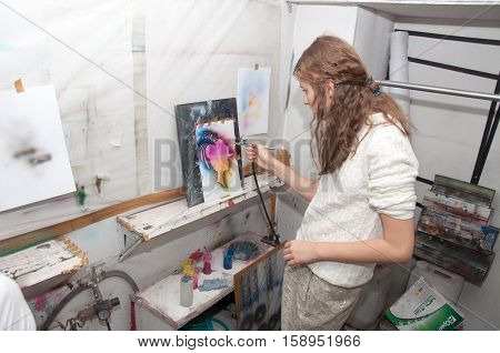 a girl teenager engaged in airbrushing paint brightly colored pictures in a artistical studio - Russia Moscow - January 24 2016