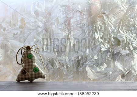 warm soft toy Christmas tree standing on a table against the window with frost / standby winter holidays