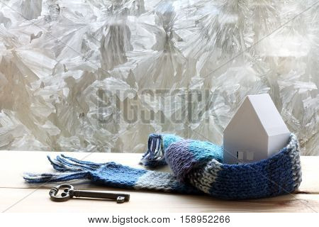layout paper house in blue scarf and a key on a background of frozen window / warming technology in construction