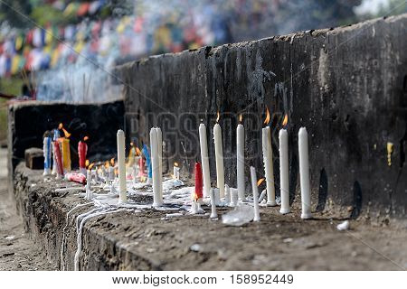 Burning and melting worship candles behind Sarnath stupa, India