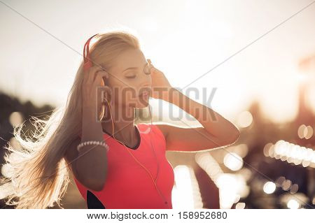 Portrait of a sporty adolescent girl resting from exercising, using listening to music with headphones, smiling outdoors. Fitness and sport lifestyle, sunny flare exterior