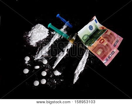 Injection syringe on cocaine drug powder lines, cocaine pile and pills and euro money bills on black background