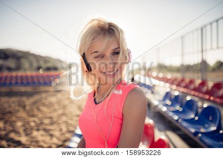 Smiling beach volleyball female player portrait with earphones