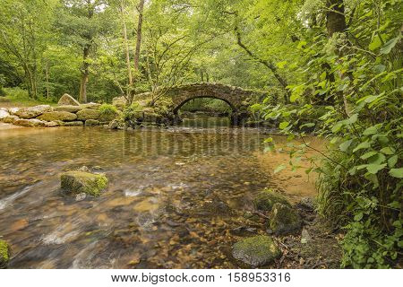 An image of an ancient packhorse bridge situated on the river Bovey Dartmoor Devon UK.