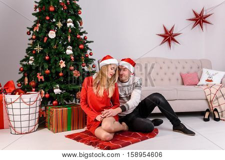 Young man and woman sitting hugging near the Christmas tree in the of Santa Claus hat