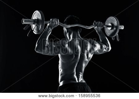 Rear view studio shot of a bodybuilder lifting a barbell on black background. Black and white color