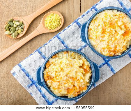 millet porridge with pumpkin in blue bowl on a kitchen towel, pumpkin seeds and millet in a wooden spoons  on a wooden table top view