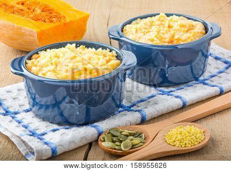 millet porridge with pumpkin in blue bowl on a kitchen towel, pumpkin seeds and millet in a wooden spoons and pumpkin on a wooden table