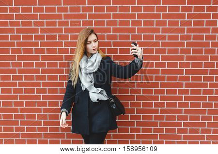 Outdoor portrait of pretty student girl taking a selfie on mobile phone. Autumn