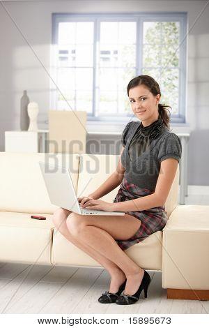 ラップトップを使用して自宅でソファに座って美少女笑みを浮かべてしますですか?。