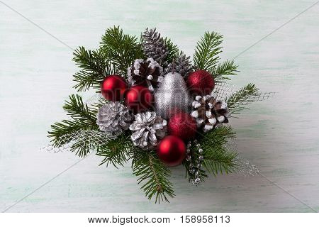 Christmas wreath with silver glitter pear and red ornaments. Christmas table centerpiece with pine cones.