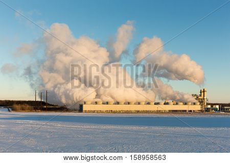 Public power plant billows steam into the clear blue winter sky as it converts natural gas to electricity. Snow on the ground. Copy space in snow if needed.