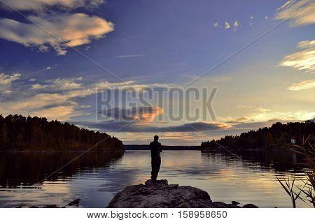 One man standing ashore lake during sunset