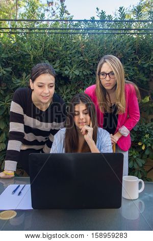 Young entrepreneurs working with a laptop. They are three beautiful Caucasian girls who are creating their company. They work on the terrace of their house.