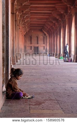 FATEHPUR SIKRI, INDIA - FEBRUARY 15 : A poor girl eating in Fatehpur Sikri complex, Uttar Pradesh, India on February, 15, 2016.
