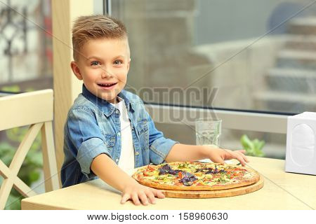 Cute boy with hot pizza in restaurant