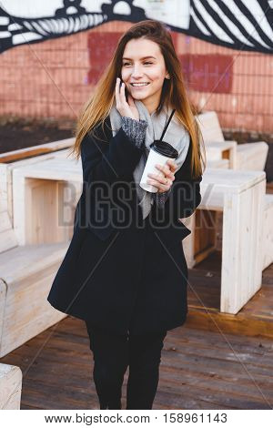 Happy young teenage woman talking on the phone laughing with a takeaway coffee cup