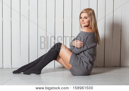 Slim attractive blonde caucasian woman with perfect makeup sitting on floor near neutral colored wooden wall. Girl clothed grey sweater and gaiters
