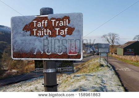 PONTSTICILL, BRECON BEACONS NATIONAL PARK, WALES, 27 APRIL 2016. Editorial photograph of Taff Trail route sign in snow. The Taff Trail runs from Cardiff Bay to Brecon and is popular amongst cyclists as well as walkers.
