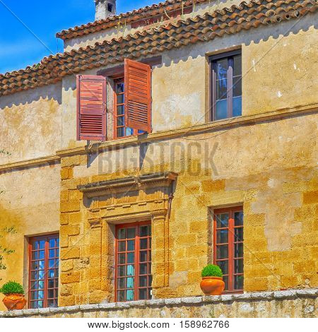 Beautiful rural sandstone house with shutter windows in Saint-Paul de Vence, Provence, France. Square toned image