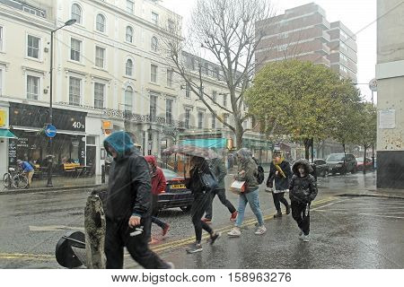 LONDON UK - March 27: Rainy day with people running on the street to find cover in London UK - March 27 2016; Rain falling in London showing typical weather condition with people on street carrying umbrellas or wearing hoodies for cover.