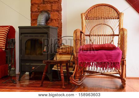 Resting corner with wicker chair besides wood stove small pile of firewood and some stove accessories