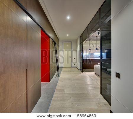Hall in a modern style with light walls, glass partitions and partially concrete ceiling. There are wooden lockers and wardrobes, ladder, door, sofa, glowing kitchen zone with hanging lamps.