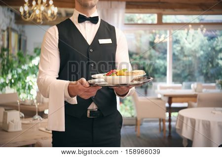 Waiter serving salad at restaurant, close up view